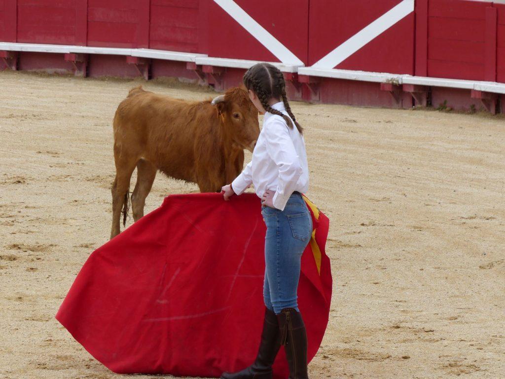 une fille avec une cape et un taureau