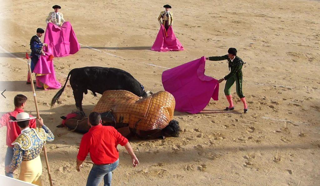 un cheval couché un taureau et des hommes